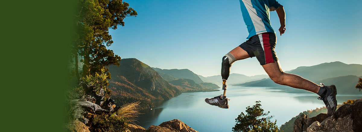 man with prosthetic leg jumping on a trail with a wilderness lake landscape
